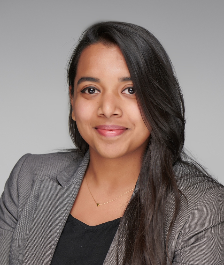 Professional headshot of smiling Indian woman in grey blazer and black blouse.